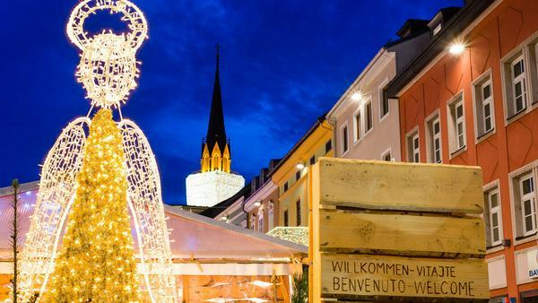 Adventmarkt in Villach mit der Kirche als Riesenkerze