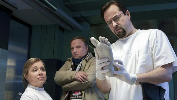 """Hat Prof. Boerne (Jan Josef Liefers, r.) diesen Fuß mit einer Fehlbildung nicht schon einmal gesehen? Silke """"Alberich"""" Haller (Christine Urspruch, l.) und Frank Thiel (Axel Prahl) sind skeptisch."""
