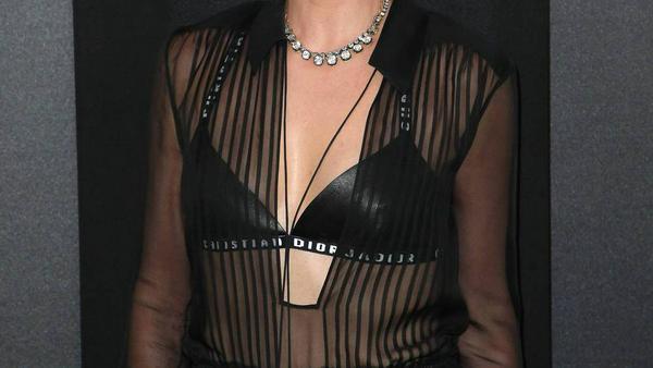 Charlize Theron trägt unter der transparenten Bluse einen sportlichen Bralette von Calvin Klein