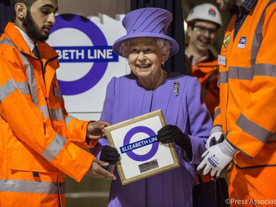 Stolz hält Queen Elizabeth II das Schild der neuen U-Bahn-Linie mit ihrem Namen hoch