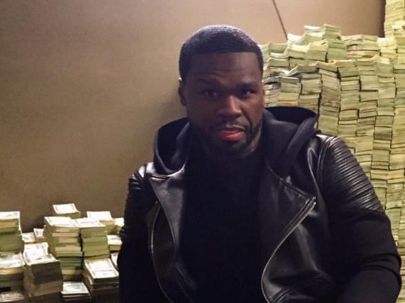 50 Cent sitzt lässig vor einem Berg aus Geldscheinen.