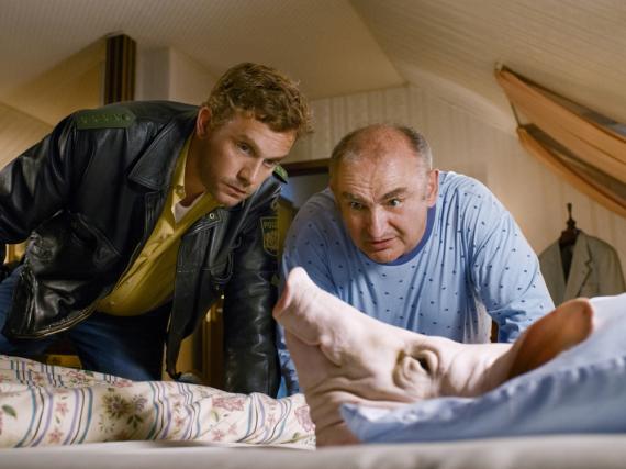 Franz (Sebastian Bezzel, l.) und Moratschek (Sigi Zimmerschied, r.) staunen über den Schweinskopf in Moratscheks Bett