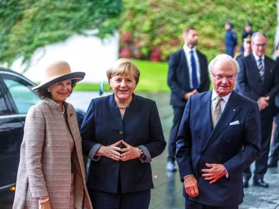 Gut gelaunt im Regen: Angela Merkel, Königin Silvia (li.) und Carl Gustaf beim gemeinsamen Treffen in Bundeskanzleramt
