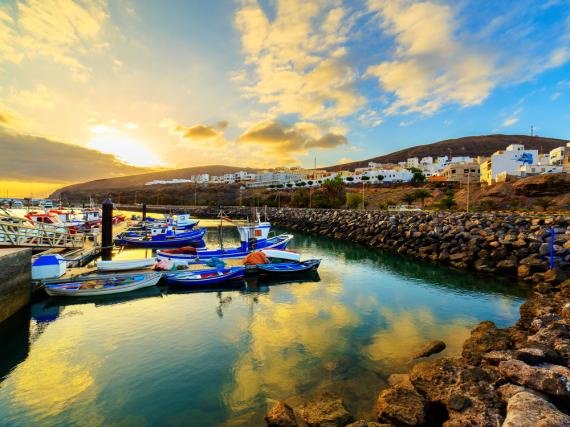 Malerische Sonnenuntergänge, wie hier über dem Hafen der Ortschaft Gran Tarajal, sind auf den Kanarischen Inseln keine Seltenheit