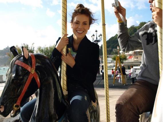 Strahlend sitzt Alyssa Milano auf dem Holzpferd