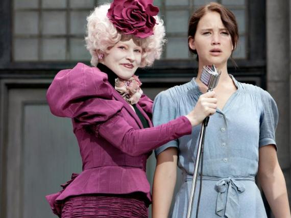 Katniss (Jennifer Lawrence, r.) meldet sich freiwillig für die Arena. Moderatorin und Betreuerin Effie Trinket (Elizabeth Banks, l.) ist begeistert.