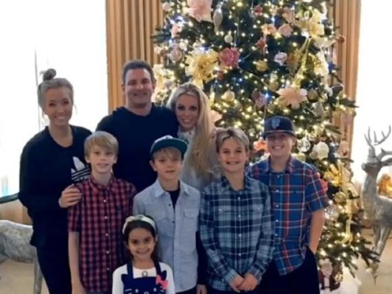 Britney Spears mit ihrer Familie vor dem prachtvoll geschmückten Weihnachtsbaum.