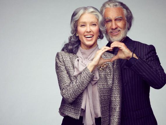 Rebecca Mir und Massimo Sinató blicken mit einem Lächeln in ihr älteres Spiegelbild